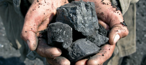 Two hands holding coal