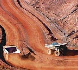 Mining dump trucks drive on red dirt road